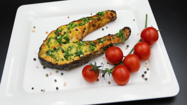 vídeos de stock e filmes b-roll de baked salmon steak in a white plate with cherry tomato isolated on black background - filete de salmão
