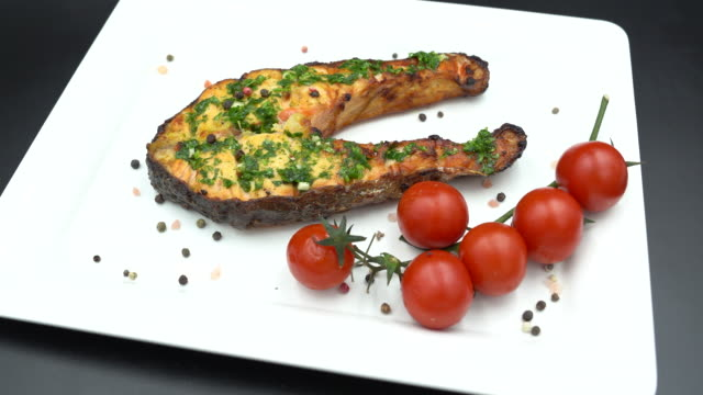 baked salmon steak in a white plate with cherry tomato isolated on black background stock video - salmon steak stock videos & royalty-free footage