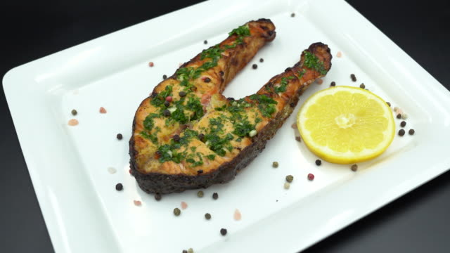 baked salmon steak in a white plate with lemon - salmon steak stock videos & royalty-free footage