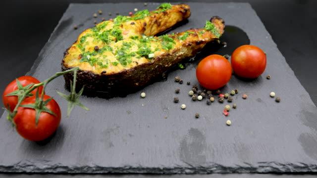 vídeos de stock e filmes b-roll de baked salmon steak isolated on black background - filete de salmão