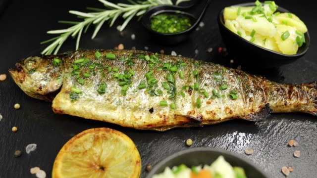 baked sea bass isolated on black background with lemon rosemary and salad - sea bass stock videos & royalty-free footage