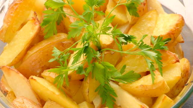 baked sliced potatoes with sprig of parsley - parsley stock videos and b-roll footage