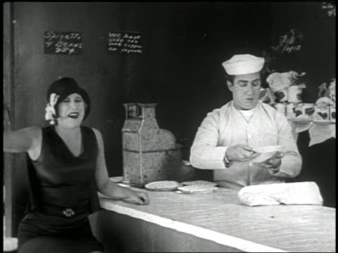 b/w 1920 baker at counter throwing pie into face of flapper sitting next to him / short - anno 1920 video stock e b–roll