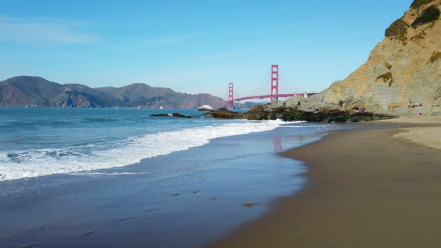 Baker Beach in San Francisco Bay and Golden Gate Bridge on background.