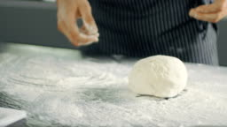 Baker Chef of Famous Restaurant Kneads the Dough in a Modern Looking Kitchen.