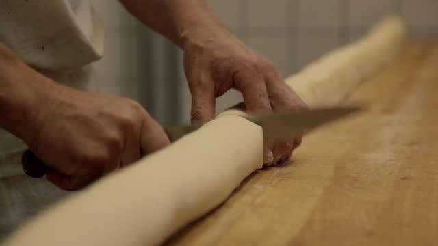 CU Baker cuts dough with a knife, close up / Copenhagen, Seeland, Denmark