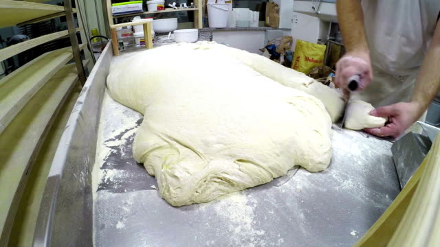 Baker cutting leavened bread dough