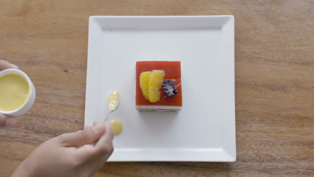 Baker decorates gourmet dessert dish with dots of yellow cream