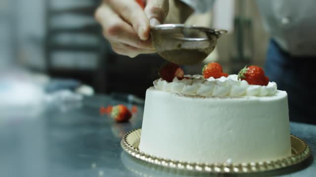 stockvideo's en b-roll-footage met baker die cake met aardbeien en het berijpen verfraait - decoration