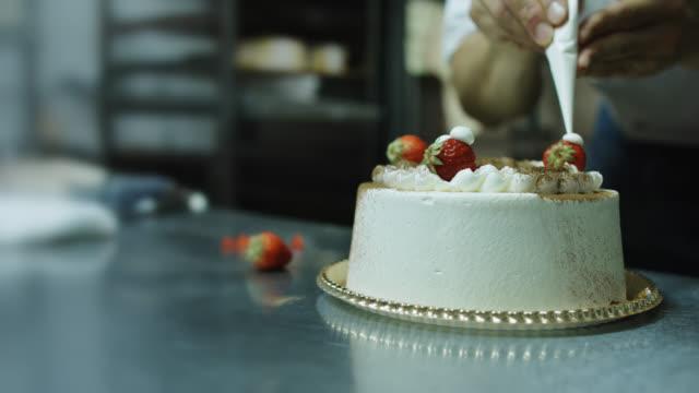 stockvideo's en b-roll-footage met baker die cake met aardbeien en het berijpen verfraait - slowmotion