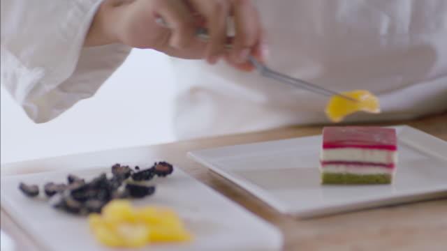 Baker delicately garnishes gourmet cake with tangerine slices