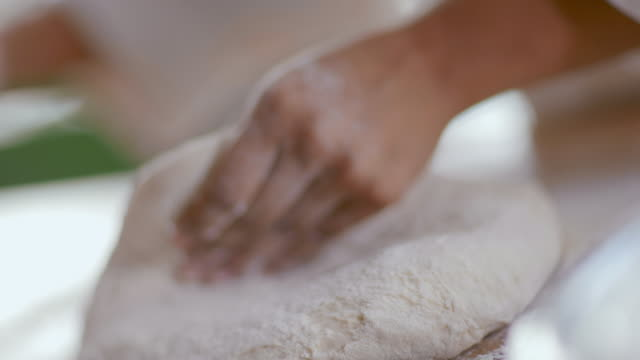 Baker flattens dough with rolling pin