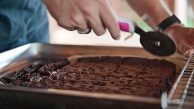 baker hand using wheel cutter cutting on baked dark chocolate chip brownies in tray - chocolate chip stock videos & royalty-free footage