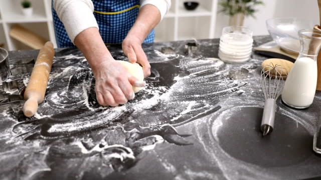 Baker hands kneading dough in flour on table