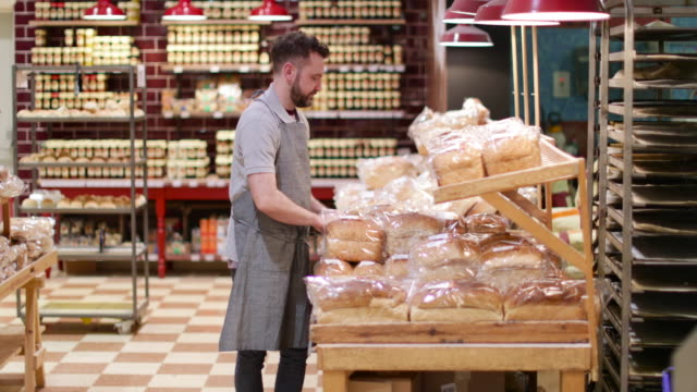baker in bakery stocking shelves and looking to camera - baker occupation stock videos and b-roll footage