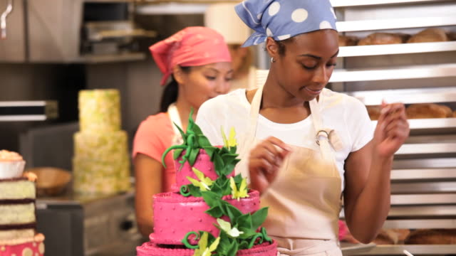 ms tu baker in commercial kitchen applying icing flowers to large cake / richmond, virginia, usa - decorating a cake stock videos and b-roll footage