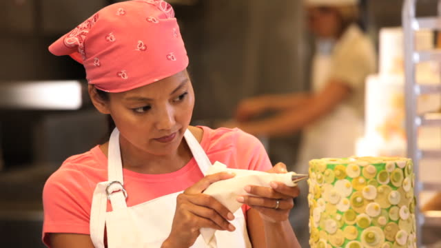 cu pan baker in commercial kitchen applying icing to large cake / richmond, virginia, usa - decorating a cake stock videos and b-roll footage