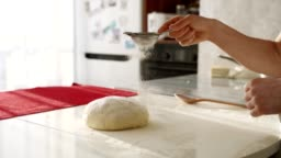 Baker kneading dough in flour on table. Close up of female hands working with dough
