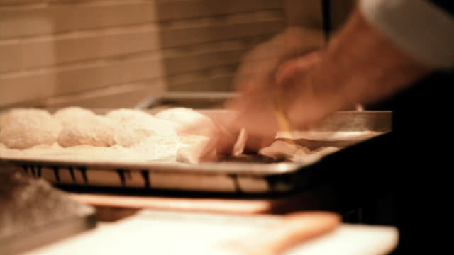 a baker pats down rounds of dough on a baking sheet. - baking sheet stock videos & royalty-free footage