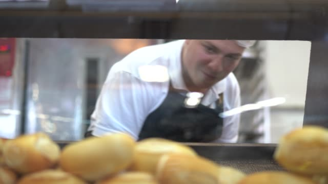 Baker picking fresh bread in bakery