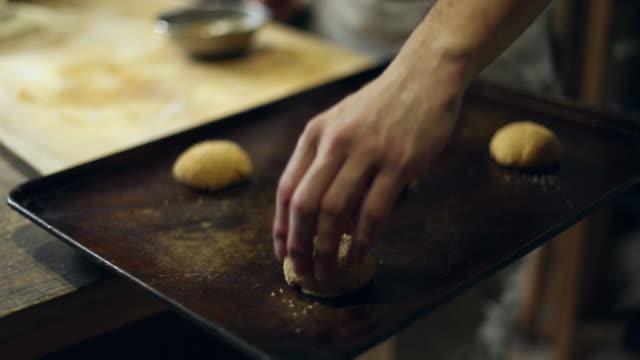 a baker placing dough onto a baking sheet - baking sheet stock videos & royalty-free footage