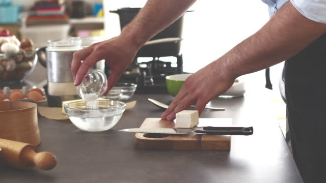 Baker pouring sugar in the bowl of water, cutting yeast
