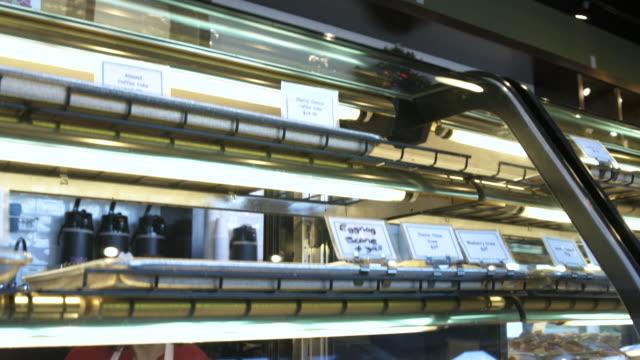 baker putting cakes into a display case - skåp med glasdörrar bildbanksvideor och videomaterial från bakom kulisserna