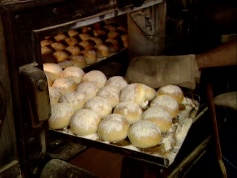 baker removes tray of rolls from oven - tipo di panino video stock e b–roll