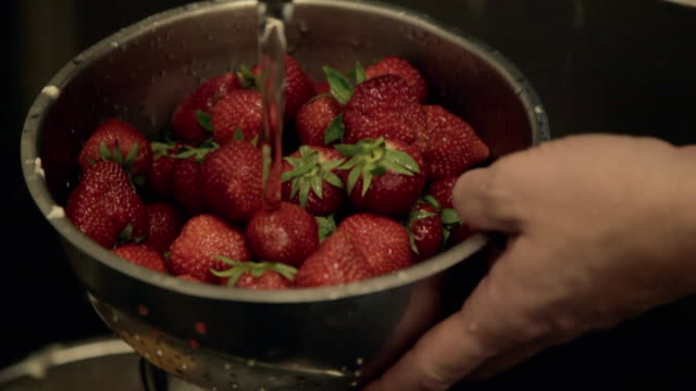 cu ts baker rinsing strawberries / copenhagen, seeland, denmark    - bowl stock videos & royalty-free footage