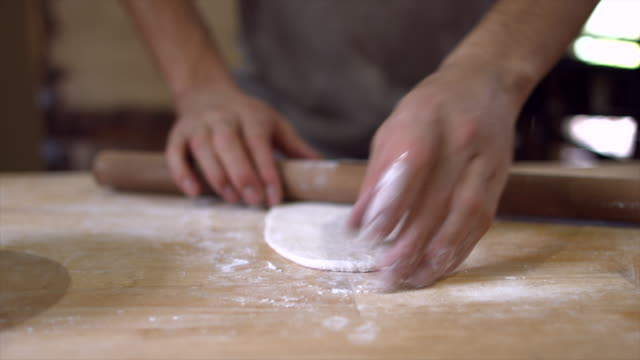 A baker rolling bread dough with a rolling pin
