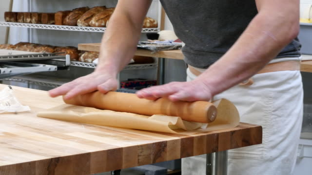 MS Baker rolling butter for croissant dough at table in bakery