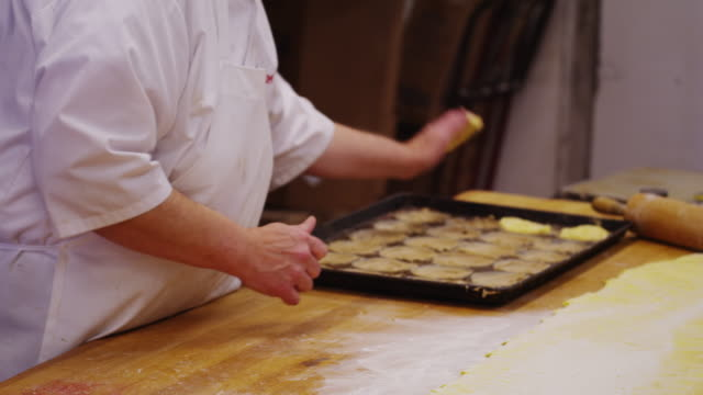 baker rolls dough and places in a pan in preparation of danish pastries. - positioning stock videos and b-roll footage