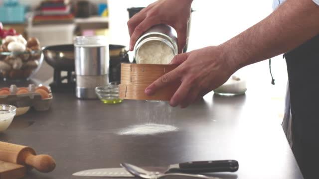 Baker setacciatura farina in cucina