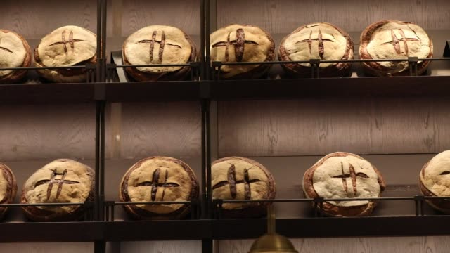 a baker slices a pattern onto loaves of bread in the food hall at the luxury department store harrods ltd in london uk on wednesday jan 10 loaves of... - pane a lievito naturale video stock e b–roll