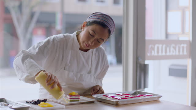 Baker squeezes dots of yellow custard around beautiful cake dish
