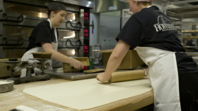 baker stretching dough with a rolling pin - rolling pin stock videos & royalty-free footage