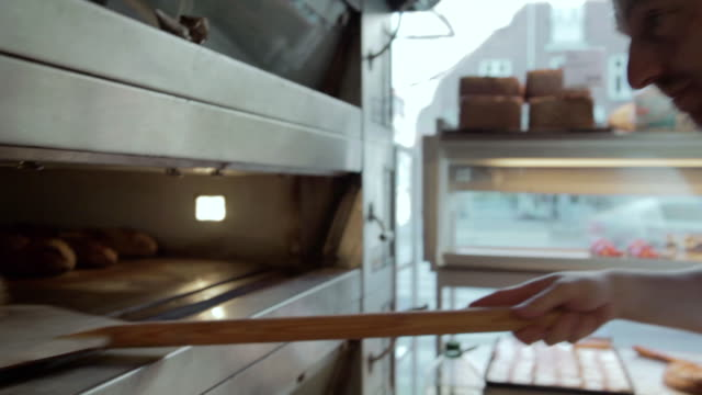 ms pan baker taking bread out of oven / copenhagen, seeland, denmark    - bakery stock videos and b-roll footage