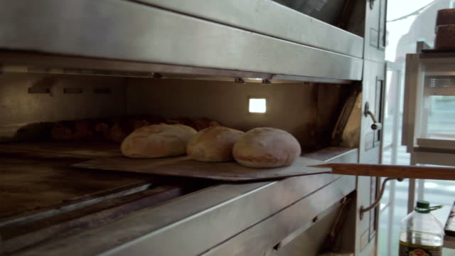 ms ts baker taking bread out of oven / copenhagen, seeland, denmark    - bread stock videos and b-roll footage