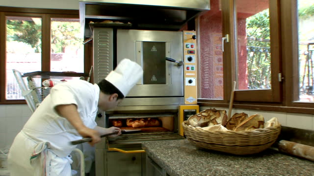 vidéos et rushes de ms baker taking bread out of oven / porto ercole, tuscany, italy - taking off