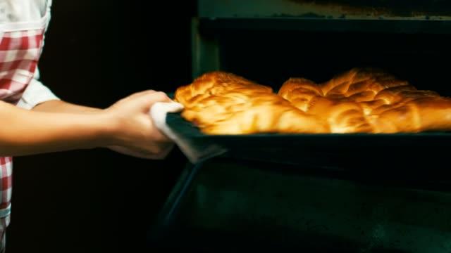 vídeos de stock e filmes b-roll de baker taking out baked pastry from oven - padaria