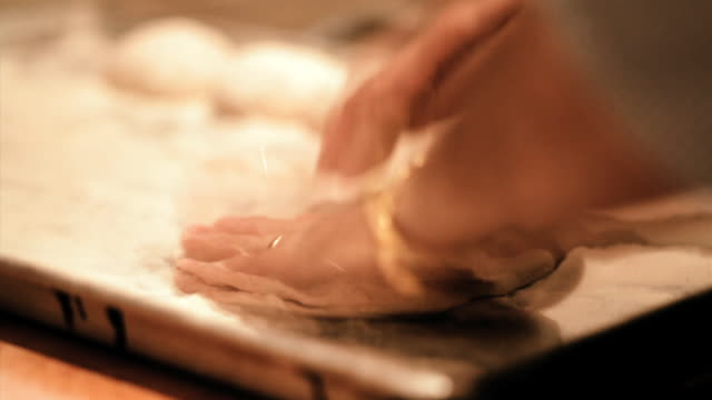 a baker taps a round of dough on a baking sheet. - baking sheet stock videos & royalty-free footage