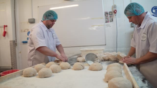 bakers are seen working at the bread factory on april 14 2020 in london england during the covid19 outbreak and lockdown the bakeryandcafe chain says... - preparing food stock videos & royalty-free footage