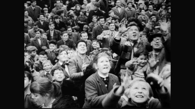 stockvideo's en b-roll-footage met / bakers dump hundreds of rolls in the back of a van / huge crowd of children stand below bakers on a hillside / bakers throw the bread rolls into... - 1957
