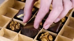 Baker's hands put handmade chocolate candies in a beautiful box.
