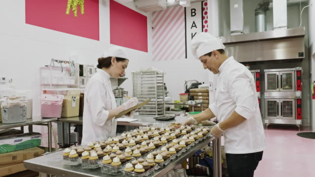 bakers icing vegan cupcakes and performing quality control - artisanal food and drink stock videos & royalty-free footage