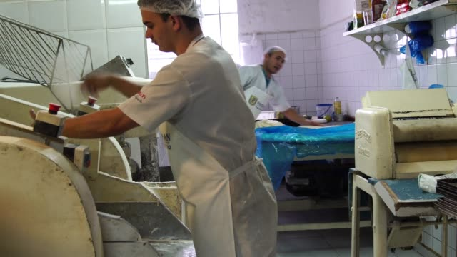 bäcker arbeiten in der professionellen küche in bäckerei - bäckerei stock-videos und b-roll-filmmaterial