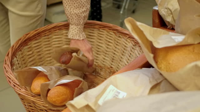 bakery aisle in supermarket. woman baying loaf of white bread - white bread stock videos and b-roll footage