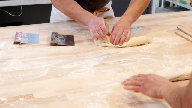 vídeos de stock e filmes b-roll de ms bakery owner showing employee how to shape dough for baguettes - guidance