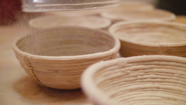 bakery powdering flour over ferment baskets - wood grain stock videos and b-roll footage