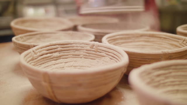 bakery powdering flour over ferment baskets - flour stock videos and b-roll footage